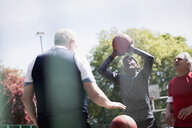 Active senior men playing basketball in sunny park - CAIF22288