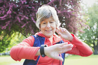 Active senior female runner checking smart watch in park - CAIF22312