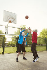 Active senior men friends playing basketball in park - CAIF22318