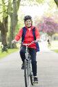 Portrait active senior woman riding bike in park - CAIF22324