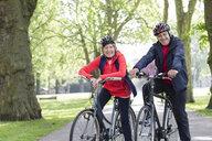 Portrait smiling, confident active senior couple riding bikes in park - CAIF22327
