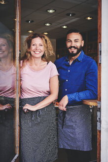 Portrait of smiling colleagues standing at store entrance - MASF09751