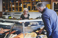 Customer showing seafood at retail display to saleswoman in deli - MASF09760