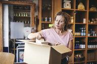 Saleswoman unpacking cardboard box in deli - MASF09775