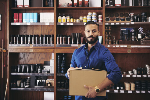 Portrait of confident salesman carrying box while standing against rack in deli - MASF09784