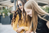 Happy female friends holding hands while enjoying in city - MASF09817