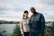 Portrait of confident male and female athlete standing on hill against sky - MASF09853
