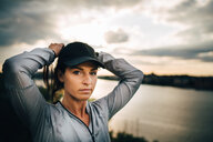 Portrait of confident female athlete tying hair while standing on hill during sunset - MASF09862