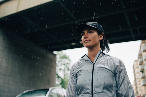 Low angle view of female athlete looking away while standing against bridge during rainy season - MASF09871