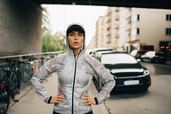 Portrait of confident female athlete in wet hooded jacket standing on sidewalk in city - MASF09874