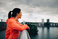 Side view of female athlete in raincoat looking away while standing on footbridge over sea - MASF09895