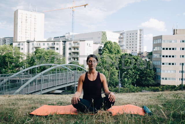 Young woman meditating on field against buildings in city - MASF09907 - Maskot/Westend61