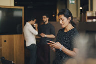 Businesswoman text messaging on smart phone with colleagues in background at office - MASF09937