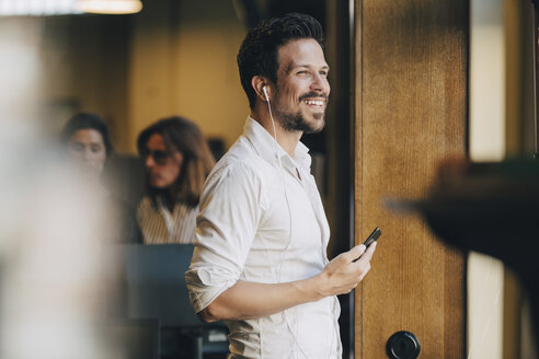 Smiling mid adult man with earphones talking on smart phone in office - MASF09940