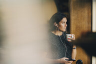 Thoughtful businesswoman drinking coffee while using mobile phone at office - MASF09946