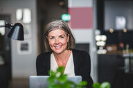 Portrait of confident businesswoman sitting at desk in creative office - MASF09970