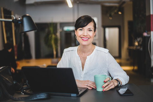 Portrait of confident businesswoman holding coffee mug while sitting at desk in office - MASF10024
