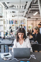 Female entrepreneur using laptop at desk in creative office - MASF10042