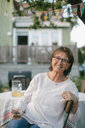 Portrait of smiling senior woman holding drink while sitting on chair at table in backyard - MASF10078