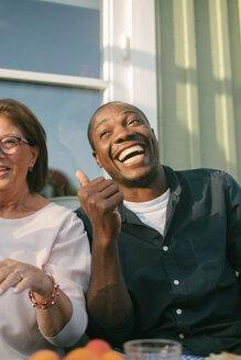Happy senior woman sitting by man at porch - MASF10084