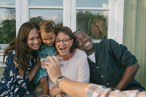 Cropped image of man showing mobile phone to cheerful family on porch - MASF10087