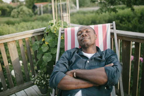 Mid adult man with closed eyes relaxing on deck chair at porch - MASF10093