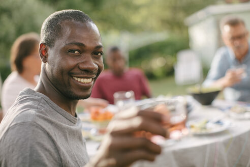 Portrait of smiling mid adult man holding drink during garden party - MASF10108