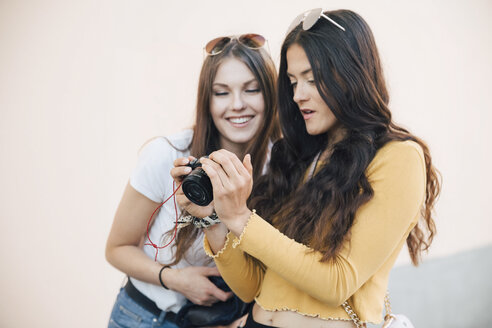Smiling young women looking at SLR Camera while standing against wall - MASF10111