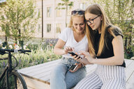 Smiling female friends sharing mobile phone while sitting on bench in city - MASF10132