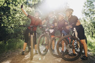 Woman taking selfie with friends while mountain biking in forest during summer - MASF10144