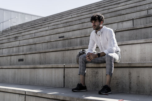 Young man with headphones sitting on stairs outdoors - GIOF04823