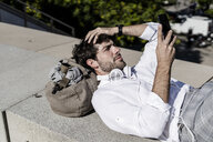 Young man lying on a wall outdoors using cell phone - GIOF04826