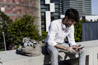 Smiling young man sitting on a bench outdoors using cell phone - GIOF04829