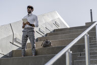 Young man standing on stairs outdoors holding tablet - GIOF04838
