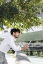 Young man leaning on railing in the city holding tablet - GIOF04841