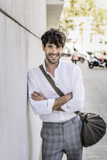 Portrait of smiling young man with bag in the city - GIOF04859