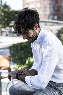 Smiling young man sitting outdoors using smartwatch - GIOF04862