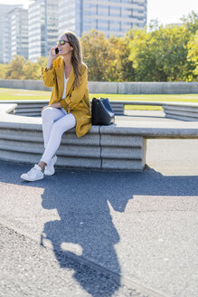 Happy woman with bag and cell phone sitting on a bench in the city - GIOF04871