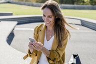Smiling woman with bag sitting on a bench in the city using cell phone - GIOF04874