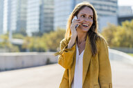 Happy woman on cell phone in the city - GIOF04880