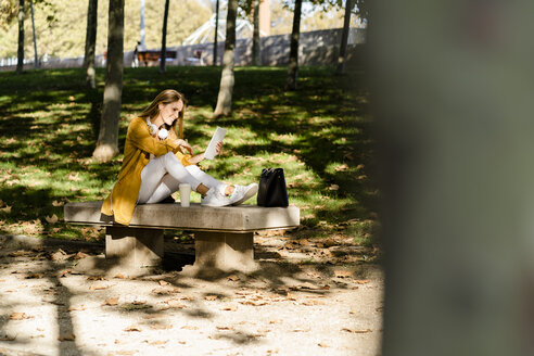 Smiling woman sitting on a bench in a park using tablet - GIOF04892