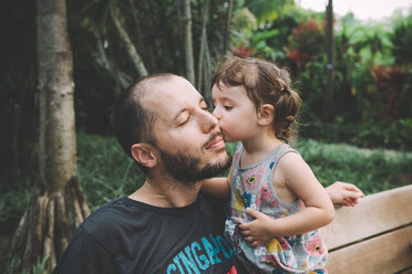 Baby girl kissing her father on cheek in a park - GEMF02637
