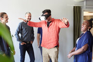 Happy business people looking at male colleague using virtual reality simulator in office - MASF10170