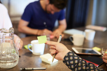 Cropped hand of businessman holding adhesive note during meeting in creative office - MASF10185