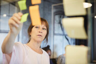 Mature businesswoman sticking sticky note on glass in creative office - MASF10191