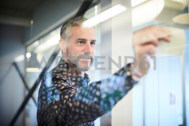 Mature businessman sticking sticky note on glass in board room - MASF10197