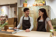 Smiling male and female coworkers standing at checkout counter - MASF10203