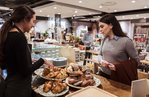 Saleswoman showing baked food to female customer at cafe - MASF10236