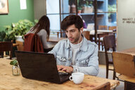 Young man using laptop while having coffee at table in cafe - MASF10245
