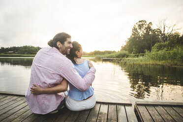 Rear view of smiling couple sitting with arms around on jetty over lake during sunset - MASF10266